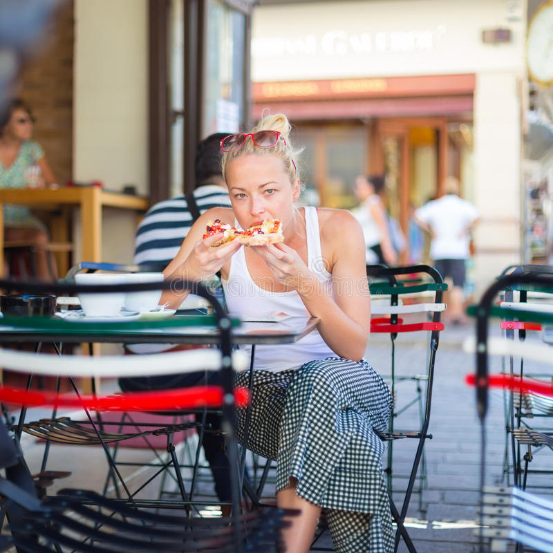 Mujer que come la pizza al aire libre en cafetería imagen de archivo