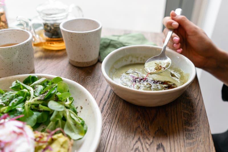 Mujer que come la sopa del detox de las verduras frescas hecha del bróculi con con las semillas de calabaza En la tostada del pri fotos de archivo libres de regalías