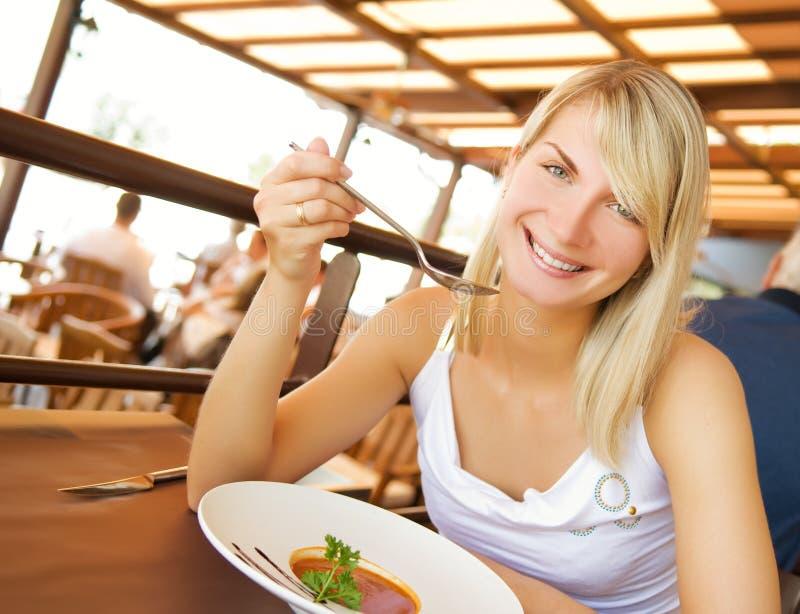 Mujer que come la sopa del tomate imagenes de archivo