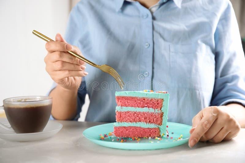 Mujer que come la torta de cumpleaños deliciosa fresca en la tabla foto de archivo