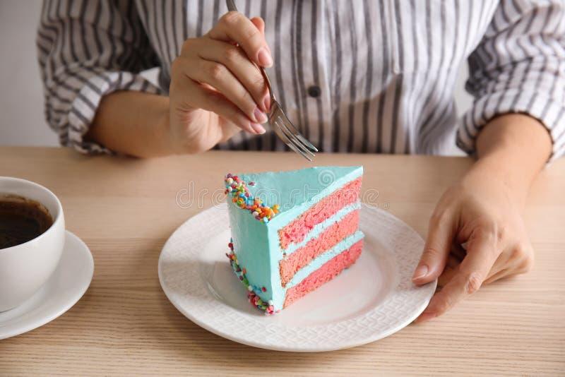 Mujer que come la torta de cumpleaños deliciosa fresca en la tabla fotos de archivo
