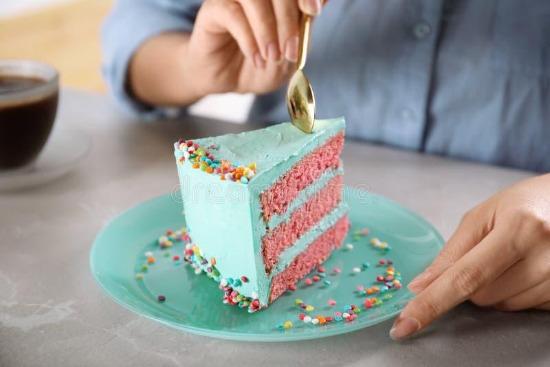 Mujer que come la torta de cumpleaños deliciosa fresca en la tabla fotografía de archivo