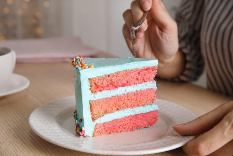 Mujer que come la torta de cumpleaños deliciosa fresca en la tabla imágenes de archivo libres de regalías