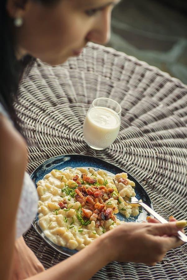Mujer que come las bolas de masa hervida de la patata con el queso y el tocino, comida eslovaca tradicional, gastronomía eslovaca imagenes de archivo