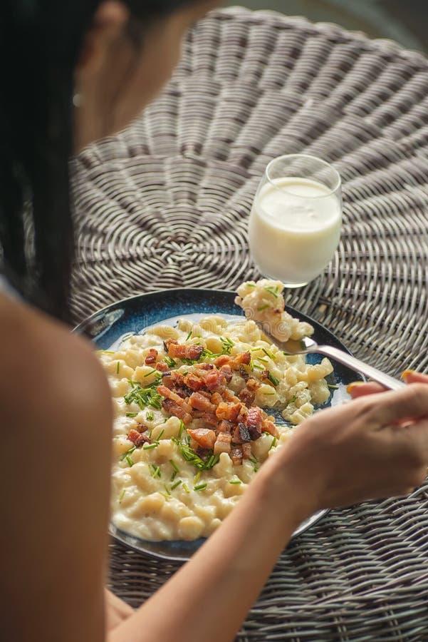 Mujer que come las bolas de masa hervida de la patata con el queso y el tocino, comida eslovaca tradicional, gastronomía eslovaca fotografía de archivo
