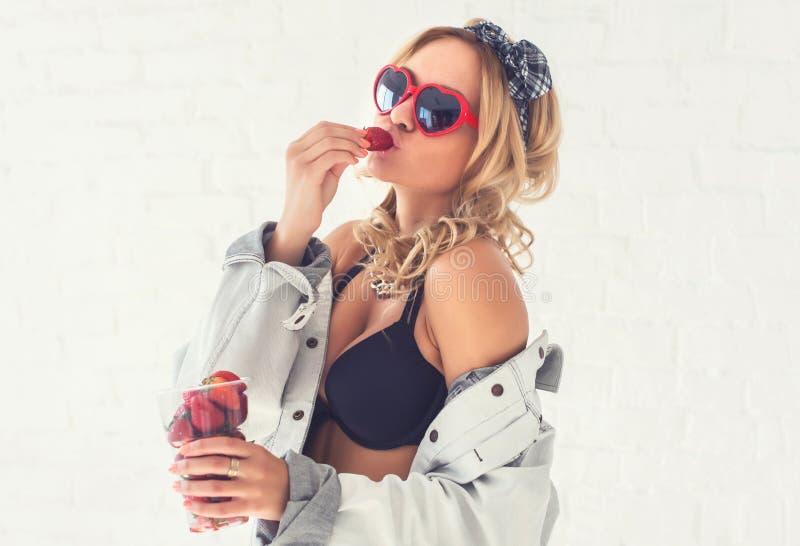 Mujer que come las fresas que miran a la forma lateral del corazón de las gafas de sol que lleva en la ropa interior y la chaquet imagenes de archivo