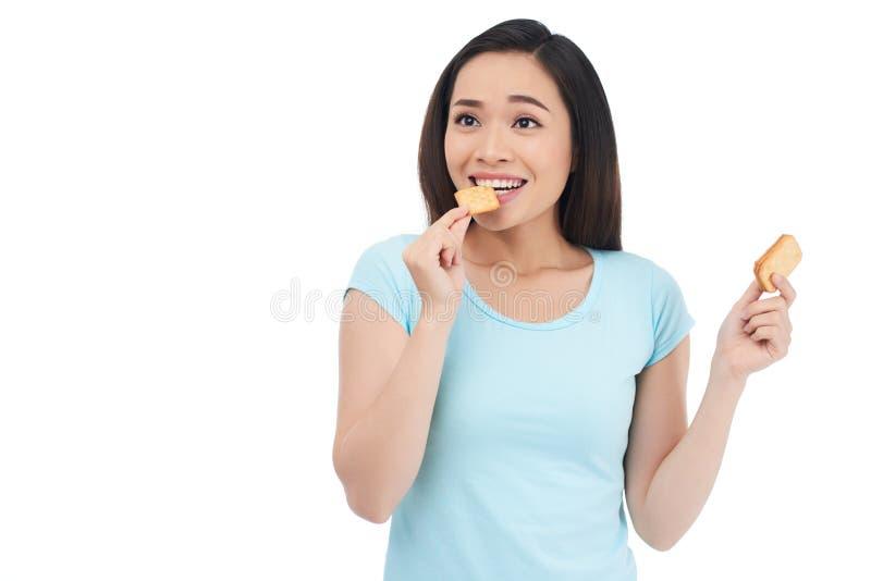 Mujer que come las galletas imagenes de archivo