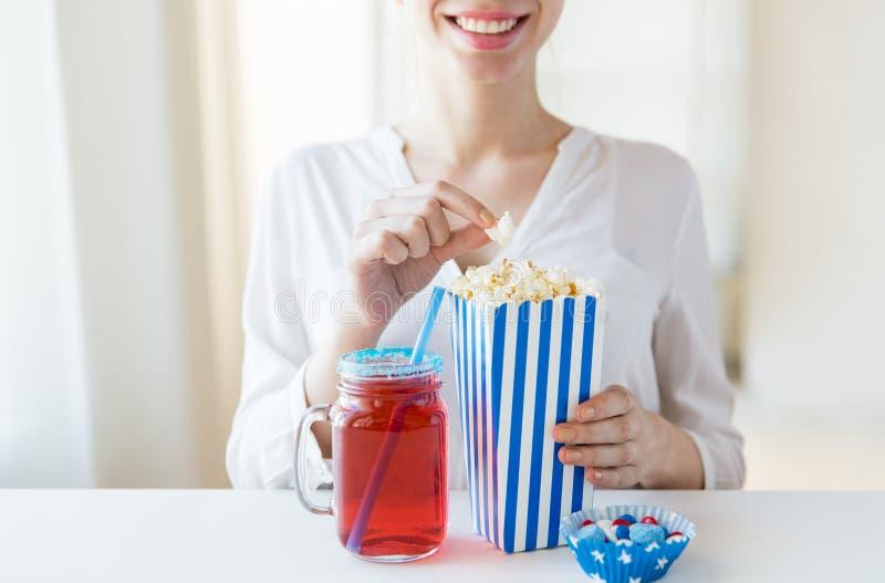 Mujer que come las palomitas con la bebida en el tarro de albañil de cristal fotos de archivo