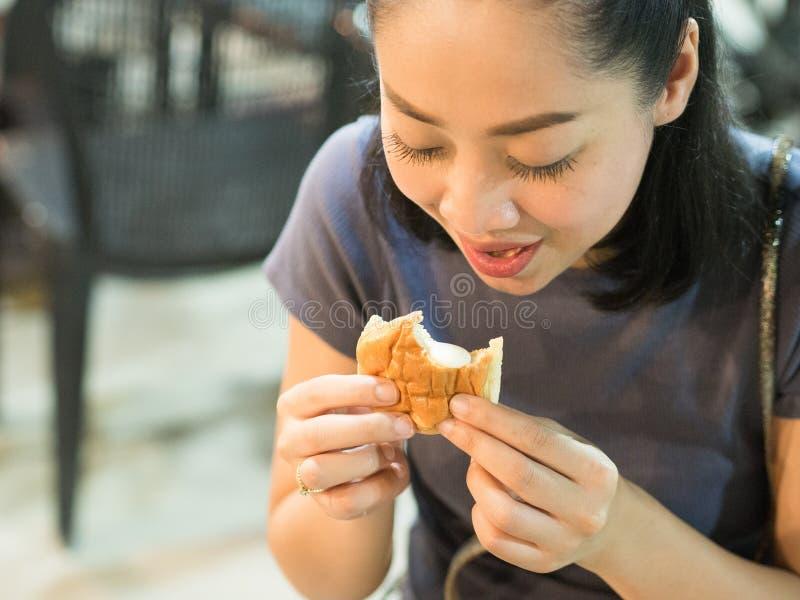 Mujer que come los bollos cremosos rellenos imagen de archivo