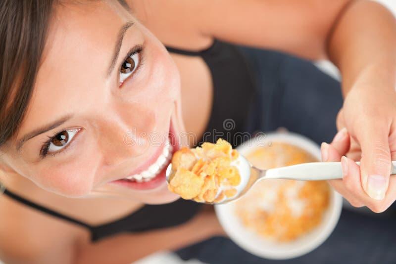 Mujer que come los cereales de los copos de maíz imagenes de archivo