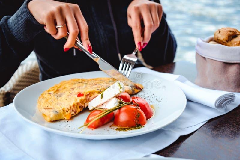 Mujer que come los huevos revueltos y el queso en restaurante imagen de archivo