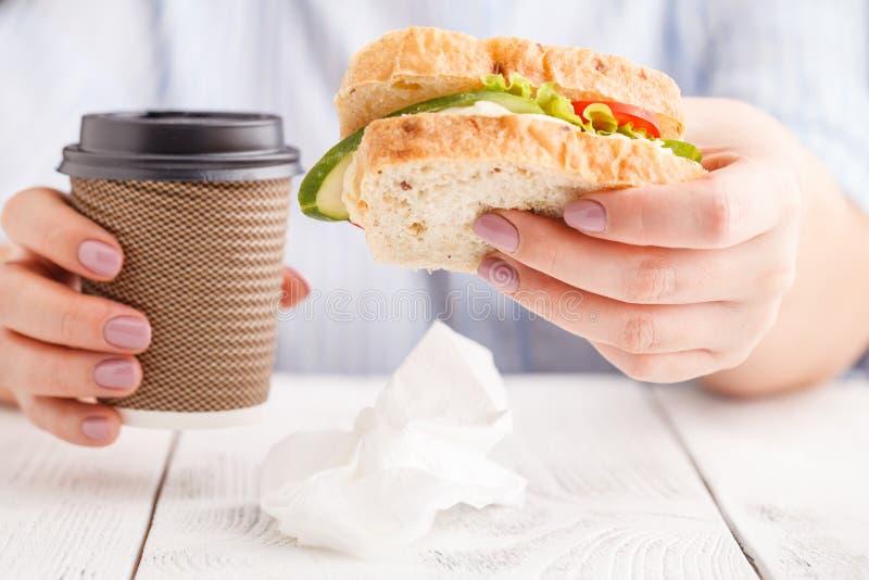 Mujer que come un bocadillo del desayuno y que bebe el café mientras que trabajo imagen de archivo