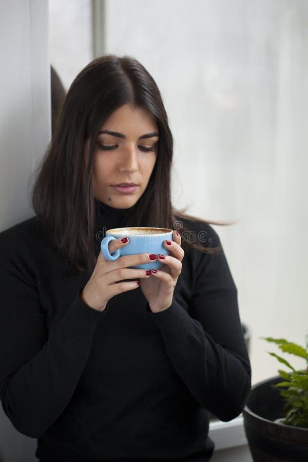 Mujer que come un café con los clavos rojos fotos de archivo