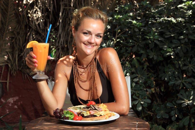 Mujer que come un cheeseburger delicioso foto de archivo