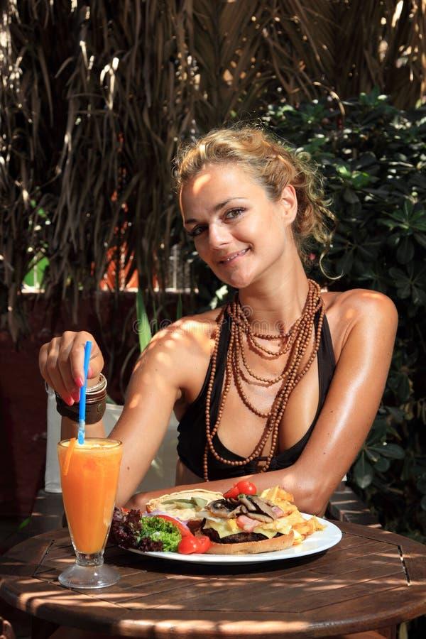 Mujer que come un cheeseburger delicioso imagen de archivo libre de regalías