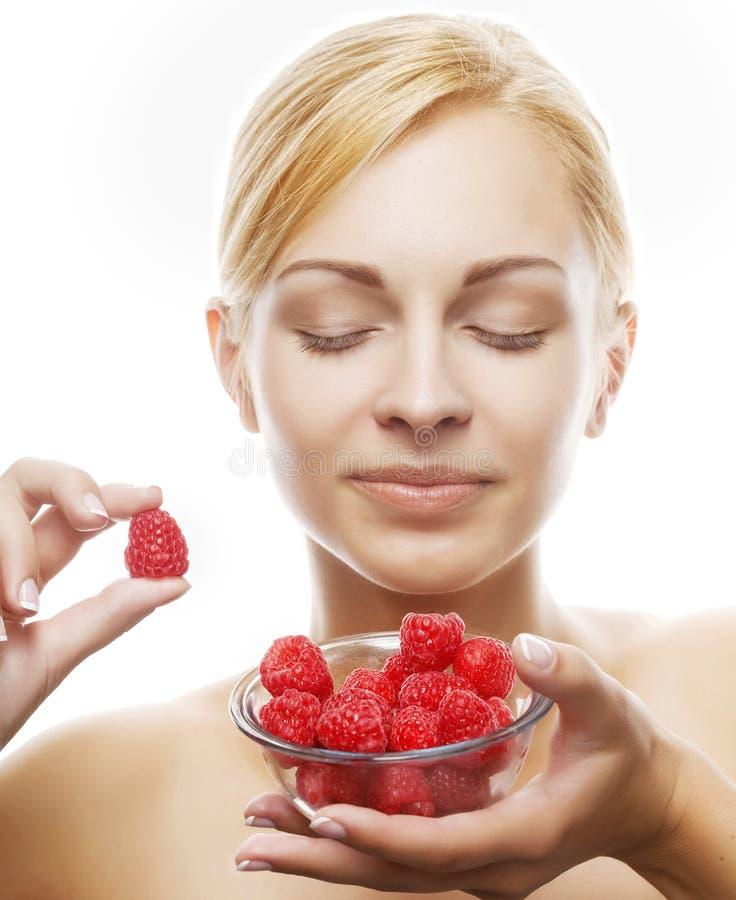 Mujer que come una frambuesa. Aislado sobre blanco foto de archivo libre de regalías
