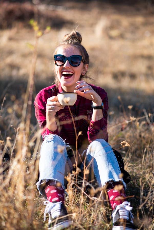 Mujer que come una taza de café al aire libre foto de archivo libre de regalías