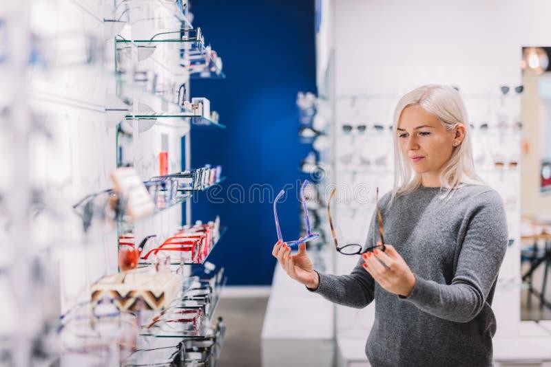 Mujer que compara los vidrios en la tienda óptica fotos de archivo libres de regalías