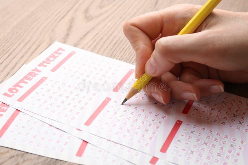 Mujer que completa boletos de lotería del lápiz en la tabla, primer Espacio para el texto imagen de archivo libre de regalías