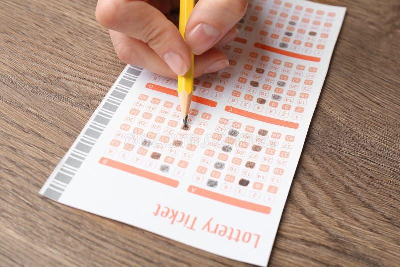 Mujer que completa el boleto de lotería del lápiz en la tabla de madera foto de archivo libre de regalías