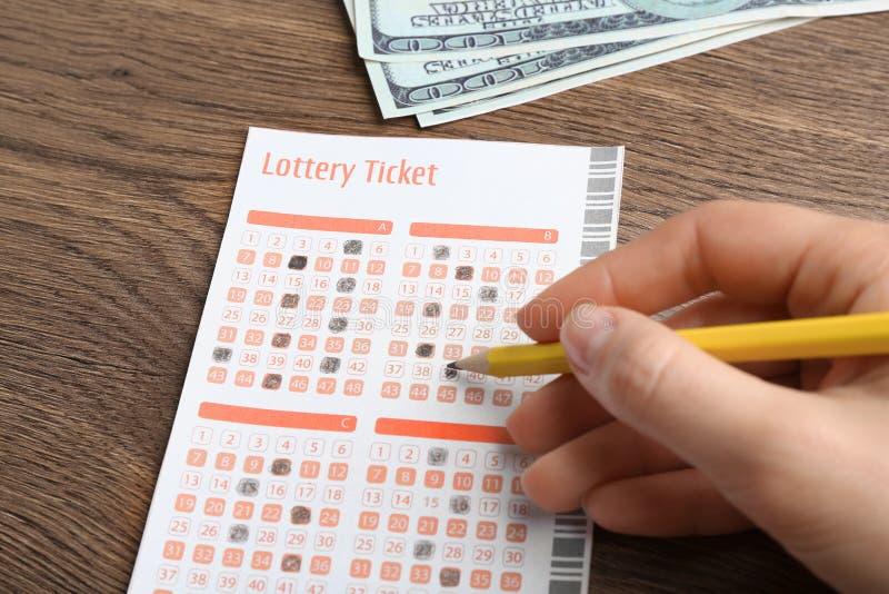 Mujer que completa el boleto de lotería del lápiz y del dinero en la tabla de madera foto de archivo