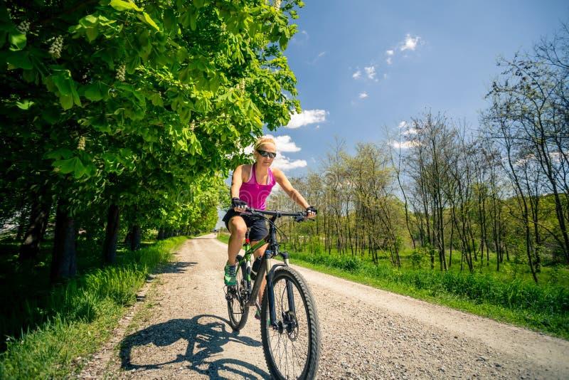 Mujer que completa un ciclo una bici de montaña en el parque de la ciudad, día de verano fotografía de archivo libre de regalías
