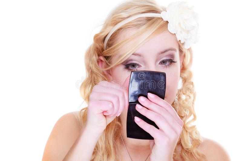 Mujer que comprueba el maquillaje que mira en espejo foto de archivo