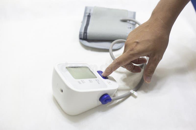 Mujer que comprueba el monitor de la presi?n arterial de la exactitud, concepto: Atenci?n sanitaria y m?dico, arterial paciente d foto de archivo