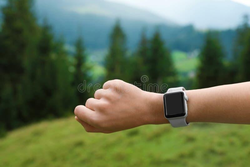 Mujer que comprueba el reloj elegante con la pantalla en blanco imagen de archivo