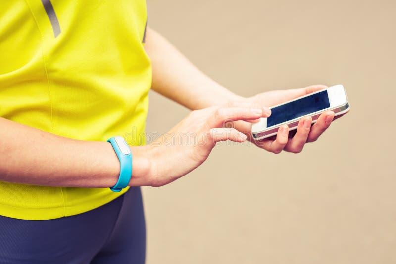 Mujer que comprueba la aptitud y la salud que siguen el dispositivo usable fotos de archivo libres de regalías