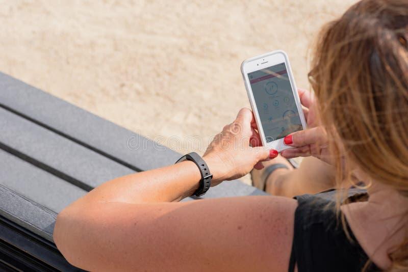 Mujer que comprueba metas de la aptitud en smartphone imagenes de archivo