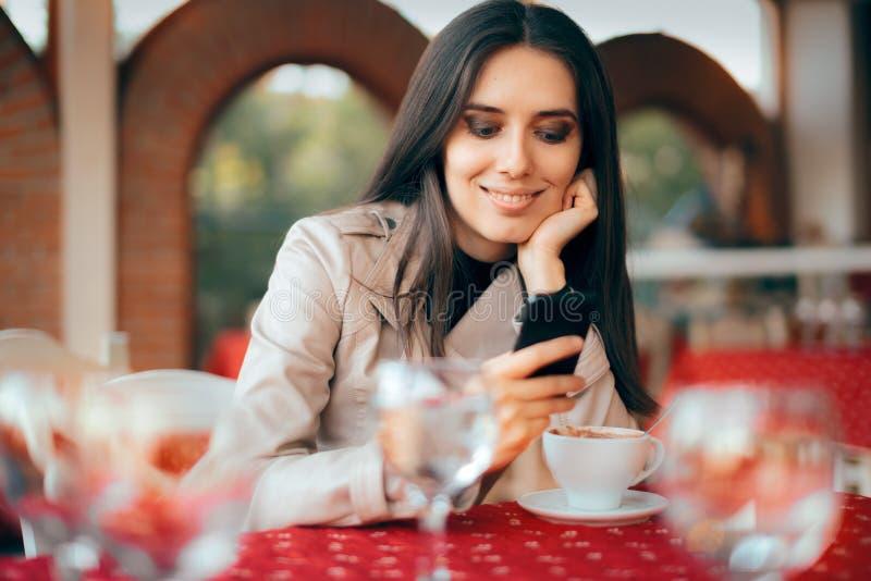 Mujer que comprueba su Smartphone en un restaurante fotos de archivo libres de regalías