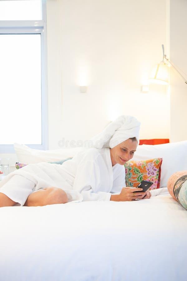 mujer que comprueba su teléfono en el dormitorio - dependencia social de los medios imagenes de archivo