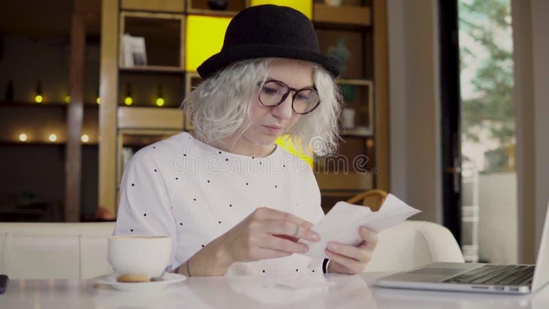 Mujer que comprueba sus costos fotografía de archivo