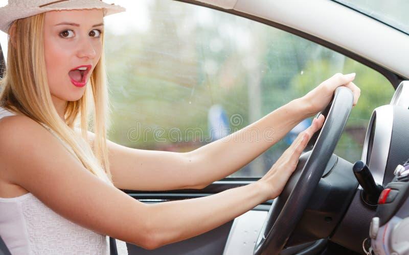 Mujer que conduce el coche con la mano en el botón de cuerno fotografía de archivo