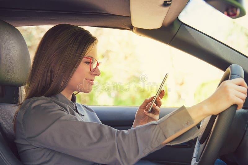 Mujer que conduce el coche y que usa el teléfono fotografía de archivo libre de regalías
