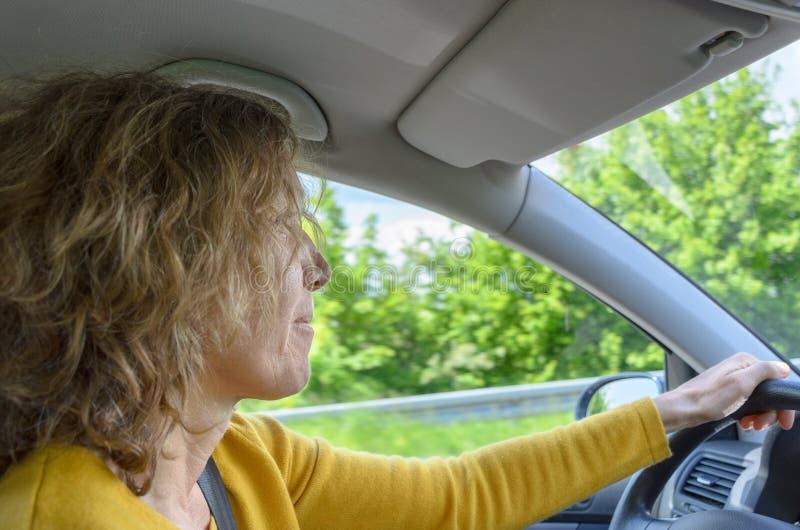 Mujer que conduce un coche aunque campo de la primavera imágenes de archivo libres de regalías
