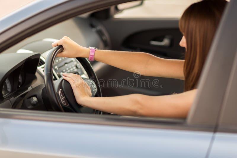 Mujer que conduce un coche con la mano en el botón de cuerno imagen de archivo