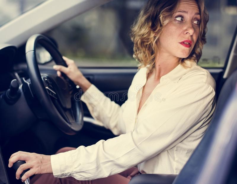 Mujer que conduce un coche en revés fotografía de archivo libre de regalías