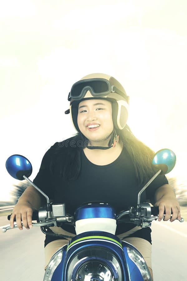 Mujer que conduce una motocicleta en el camino imagenes de archivo