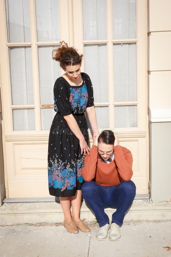 Mujer que conforta al hombre deprimido delante de la casa en el stai foto de archivo libre de regalías