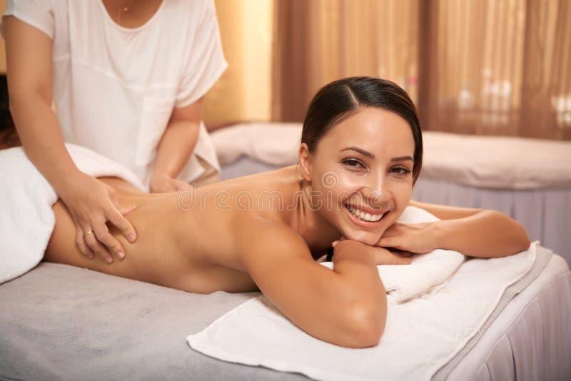 Mujer que consigue el masaje para su parte posterior imágenes de archivo libres de regalías