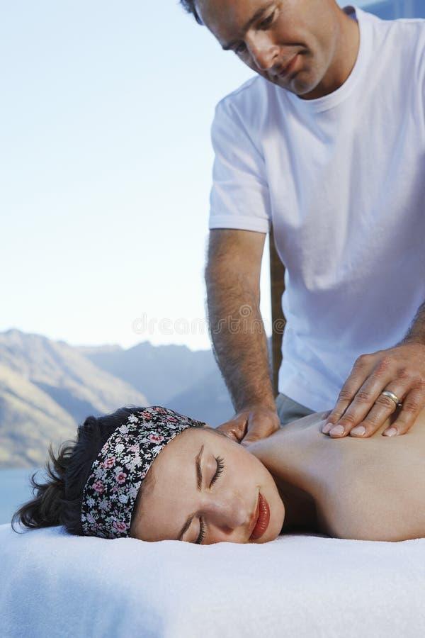 Mujer que consigue a A masaje trasero imagen de archivo