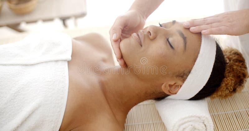 Mujer que consigue un masaje de cara fotografía de archivo