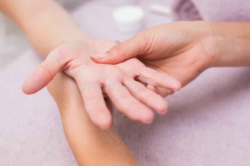 Mujer que consigue un masaje de la mano imagenes de archivo