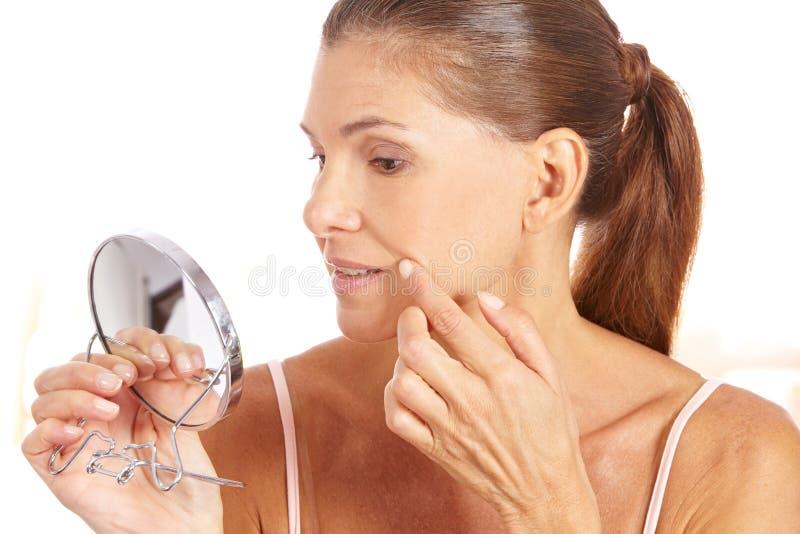 Mujer que controla arrugas en espejo foto de archivo libre de regalías