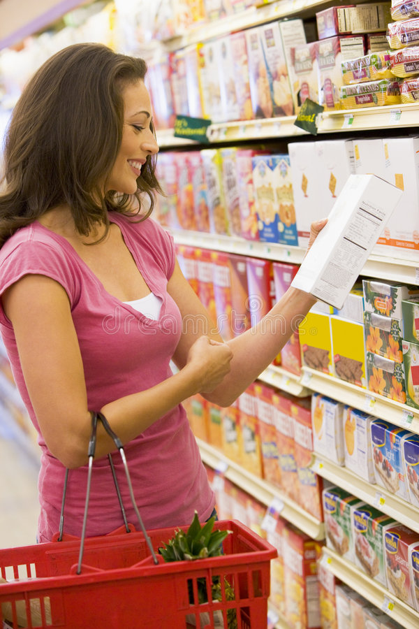 Mujer que controla el etiquetado de alimentos foto de archivo