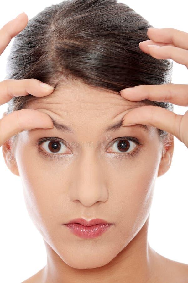 Mujer Que Controla Sus Arrugas En Su Frente Imagen de archivo libre de regalías