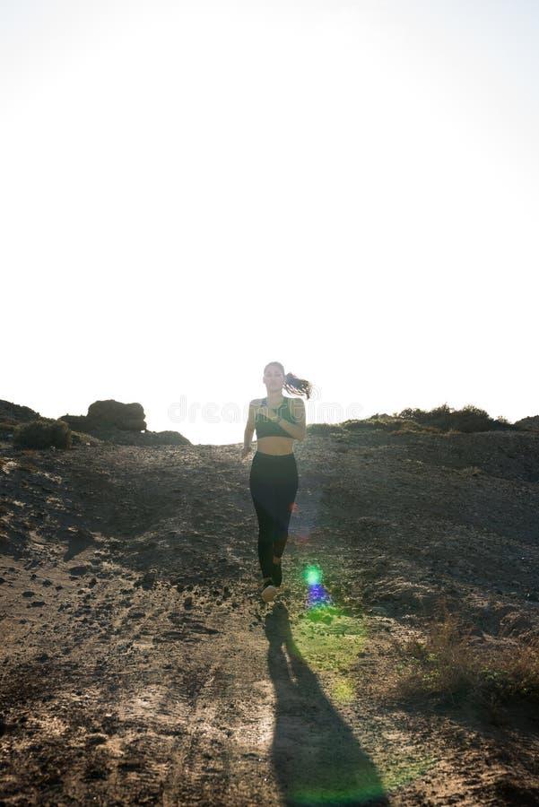 Mujer que corre con la luz del sol detrás de ella imagen de archivo