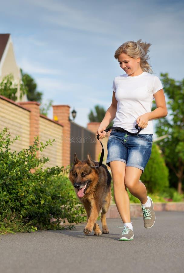 Mujer que corre con su perro fotografía de archivo libre de regalías